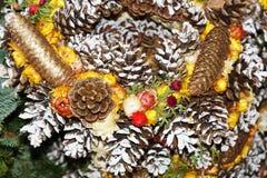 Corona di Natale con le pigne ed i fiori Immagini Stock