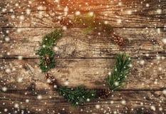 Corona di Natale dei rami dell'abete, coni su fondo di legno con i fiocchi di neve immagini stock libere da diritti
