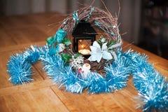 Corona di Natale dei rami sulla pelle della pelliccia con la società di un pupazzo di neve e di un cane con una candela nei prece immagini stock