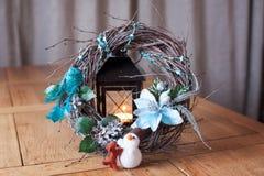 Corona di Natale dei rami sulla pelle della pelliccia con la società di un pupazzo di neve e di un cane con una candela nei prece fotografia stock
