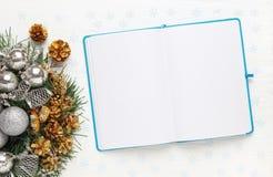 Corona di Natale e blocco note aperto in bianco su fondo bianco fotografie stock