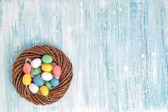 Corona di Pasqua con le uova di Pasqua variopinte su fondo blu Vista superiore, spazio della copia Fotografia Stock