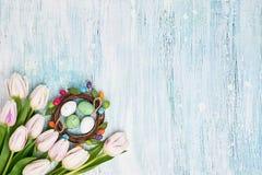 Corona di Pasqua, tulipani bianchi ed uova di Pasqua decorative su fondo blu-chiaro Vista superiore Fotografie Stock Libere da Diritti