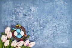 Corona di Pasqua, tulipani bianchi ed uova di Pasqua decorative su fondo blu Vista superiore Fotografia Stock Libera da Diritti