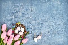Corona di Pasqua, tulipani rosa ed uova di Pasqua decorative su fondo blu Copi lo spazio Fotografia Stock Libera da Diritti