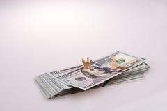 Corona disposta sull'americano 100 banconote del dollaro su bianco Immagine Stock Libera da Diritti