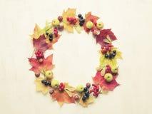 Corona fatta delle foglie di autunno, delle bacche, delle mele e dei dadi Autunno c Fotografia Stock
