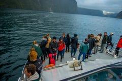 Corona non identificata della gente che enoying il bello paesaggio del ghiacciaio dell'alta montagna a Milford Sound con un bello Fotografie Stock