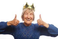 Corona que lleva de la mujer mayor que hace la acción enrrollada Imagen de archivo libre de regalías
