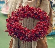 Corona rustica di natale che tiene le bacche rosse ai rami nel deposito Immagine lunatica atmosferica all'officina di festa fotografie stock