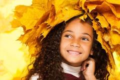 Corona sonriente de las hojas de arce de la muchacha que lleva negra Foto de archivo libre de regalías