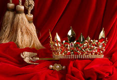 Corona y cetro en el terciopelo rojo Fotos de archivo
