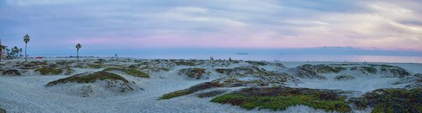 Coronado Beach in San Diego by the Historic Hotel del Coronado, at sunset with unique beach sand dunes, panorama view of the Pacif. Ic Ocean, silhouettes of royalty free stock image