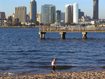 Coronado Island. Little boy playing in water on the beach on Coronado Island, with San Diego and ferry landing in the background royalty free stock photos