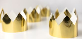 Coronas de oro de la cartulina que mienten en una tabla blanca Estilo de Minimalistic Imágenes de archivo libres de regalías