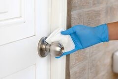 Free Coronavirus COVID-19 Prevention, Close Up Of Hand Cleaning Doorknob With Antibacterial Disinfecting Wipe For Killing Corona Virus Royalty Free Stock Image - 183134216