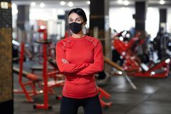 Free Coronavirus Covid-19 Prevention, Fitness Girl With A Medical Mask Posing In Gym. Fighting Viruses Royalty Free Stock Images - 175741409