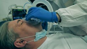 Coronavirus, covid-19 patient in intensive care unit at a hospital. One doctor plugs respiratory device while treating