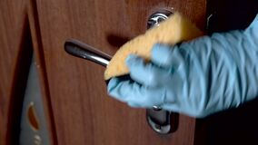Coronavirus covid-19 prevention cleaning woman wiping doorknob with antibacterial disinfecting wipe.
