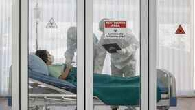 Coronavirus covid-19 quarantine and breakout alert sign on window of quarantine room at hospital with disease control experts try