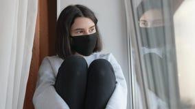 Free Coronavirus. Girl Kid Looks Out Window Sad In A Covid Medical Mask. Stay At Home. Pandemic Self-isolation Coronavirus Stock Photos - 214689623