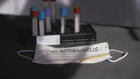 Coronavirus. Medical test tubes are in the organizer. Medical disposable gauze bandages are on the table. A mercury