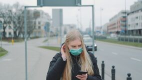 Coronavirus pandemic: blonde woman in a medical mask writing message on smartphone