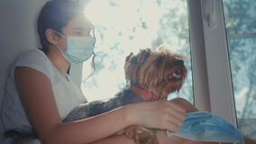Coronavirus pandemic concept. little teenage girl puts a medical mask on a dog. lifestyle self-isolation concept virus