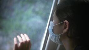Coronavirus pandemic. Little girl looks out the window sad in a medical gauze mask. Self-isolation concept virus covid