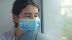 Coronavirus pandemic. little teenage girl in a medical mask with a basketball ball lifestyle is sad. self-isolation
