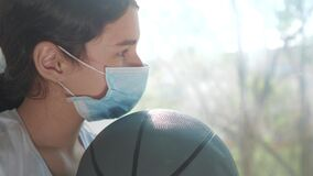 Coronavirus pandemic. little teenage girl in a medical mask with a basketball ball is sad. self-isolation concept virus