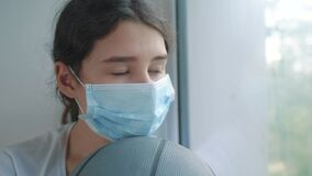 Coronavirus pandemic. little teenage girl in a medical mask with a basketball lifestyle ball is sad. self-isolation