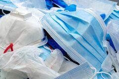 Coronavirus protection equipment in medical waste bin. Used face masks and sterile gloves.