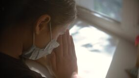 Coronavirus religion concept. little girl looks out the window sad in a medical gauze mask. faith and religion doomsday