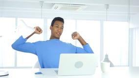 Corpo d'allungamento e di rilassamento del giovane uomo afroamericano in ufficio Fotografie Stock Libere da Diritti