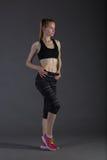 Corpo da fêmea magro no activewear que faz o posin na baixa chave cinzenta, louro perfeito Imagens de Stock