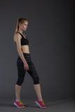 Corpo da fêmea magro no activewear que faz o posin na baixa chave cinzenta, louro perfeito Imagens de Stock Royalty Free