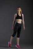 Corpo da fêmea magro no activewear que faz o posin na baixa chave cinzenta, louro perfeito Fotos de Stock