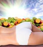 Corpo da mulher sobre frutas frescas e o céu ensolarado Foto de Stock Royalty Free