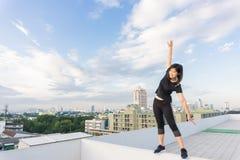 Corpo del corridore di forma fisica che fa routine di riscaldamento sulla cima del tetto che costruisce b Immagini Stock