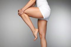 Corpo della donna? con un particolare del sole Chiuda su di belle gambe femminili con dolore in ginocchio Fotografia Stock