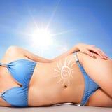 Corpo della giovane donna alla spiaggia con la crema del blocchetto del sole Fotografia Stock