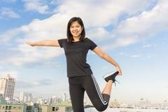 Corpo di allungamento delle donne sopra costruzione per correre Fotografia Stock