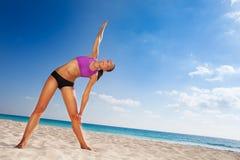 Corpo di piegamento della ragazza bella con il braccio su sulla spiaggia Fotografia Stock Libera da Diritti