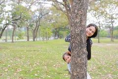 Corpo do couro cru da menina da mamã asiática feliz e da criança pequena atrás do tronco de árvore no jardim exterior imagens de stock