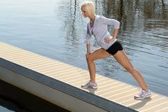 Corpo do estiramento da mulher do esporte no cais da água Fotografia de Stock