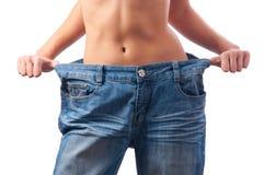 Corpo fêmea atlético em calças demasiado grandes imagens de stock