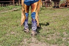 Corpo inferior de um vaqueiro nas botas com dentes retos imagem de stock