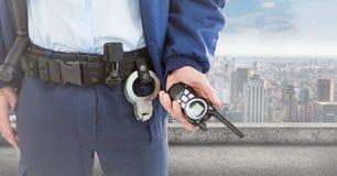 Corpo inferior do agente de segurança com o Walkietalkie contra a skyline Foto de Stock