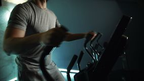 Corpo magro do atleta masculino novo, que está fazendo o exercício no cruz-instrutor no gym moderno, movimento lento filme